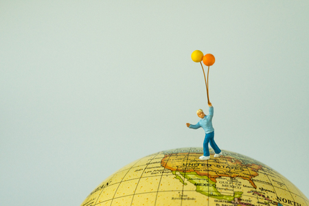 Miiniature people figure happy kid holding balloons standing on united states of america map on globe as world climate change or happy american children concept. Stock Photo