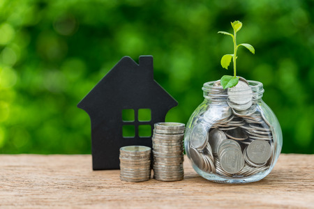Stack of coins and jar with full of coins with growth sprout plant and black house as property or mortgage investment concept.