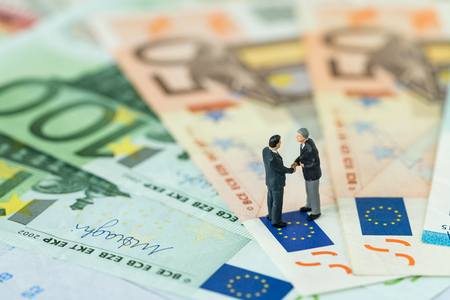 Miniature figure, agreement concept with businessmen shaking hand standing on Euro flag on pile of Euro banknotes as Euro economy discussion or Brexit negotiation concept.