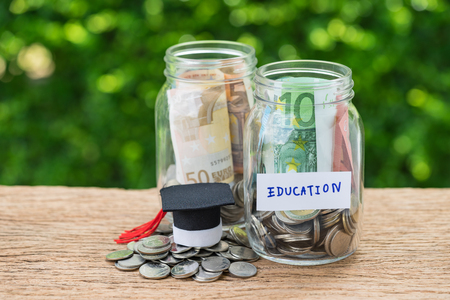 Saving for Education concept as coins in jar with text Education and mini graduation hat on wooden table and green bokeh background. Stock Photo