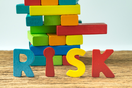 Business risk concept with colorful wooden alphabets RISK and wooden blocks tower ready to collapse in the background.