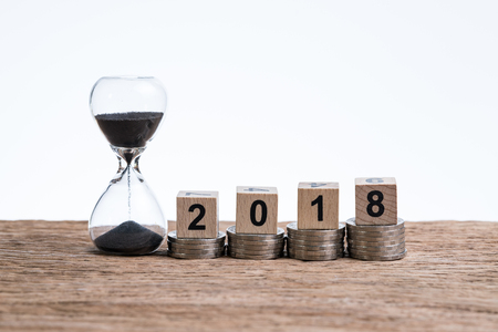Time running year 2018 financial or investment concept with hourglass or sandglass and cube block number 2018 on stack of coins put on wooden table with white background and copy space. Stock Photo