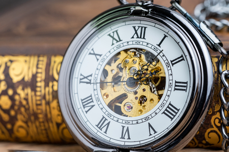 Closed up vintage pocket watch on book using as time symbol or business deadline concept.