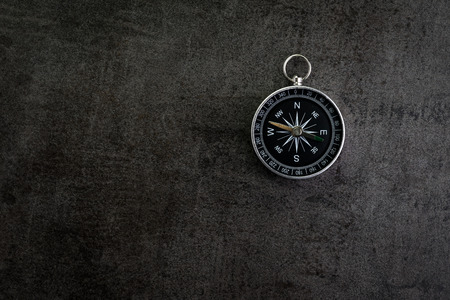 Compass on dark black textured cement with copy space using as direction, travel or adventure journey concept.