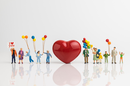 Miniature people happy love family holding balloons with red heart shape on white background using as happy valentine's day concept.
