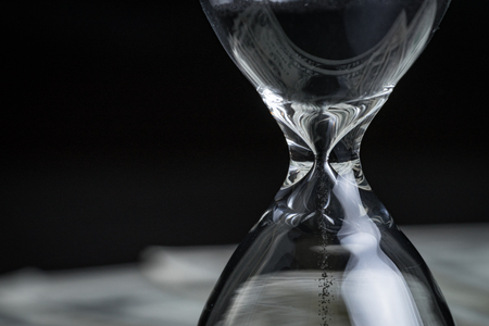 Closed up of sandglass or hourglass with reflection of US dollar banknotes on black background using as time investment or financial deadline concept.