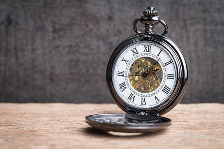 Relógio do mecânico do bolso do vintage na tabela de madeira usando-se como o símbolo do tempo ou o conceito do fim de negócio.