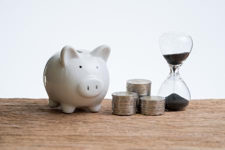 Finance ou temps d'investissement avec sablier ou sablier, tirelire et pile de pièces sur une table en bois avec un fond blanc.