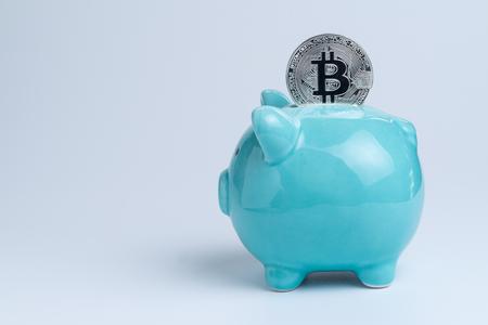 Bitcoin on blue piggy bank as crypto digital banking or cyber savings concept.