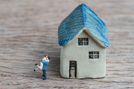 Miniature couple, happiness husband and wife with ceramic house using as success marriage life or mortgage concept.
