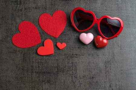 Red and pink heart shapes with heart shape eyeglasses on black cement wallpaper as Valentine's day concept with copy space. 스톡 콘텐츠