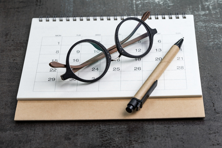 Calendar planning and year plan concept with eyeglasses and pen on clean white calendar on black background.