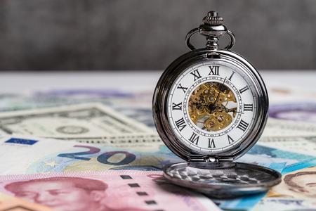 Hora para o dinheiro, contando-se para baixo para o conceito da crise financeira do mundo, relógio de bolso mecânico do vintage em cédulas internacionais principais dos países.