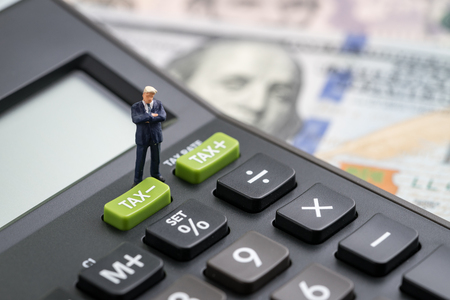 Tax cuts or reduce concept, miniature people business man president standing with TAX minus button on calculator with background of blurred US Dollar banknotes, United States government tax overhaul.