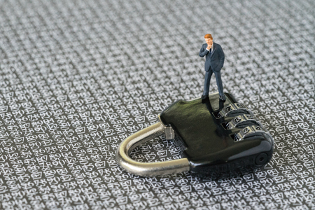 Auswirkung der Computersicherheit auf IT-Geschäftskonzept, wenn die Miniaturzahl Geschäftsmann auf Zahlenschlossauflage mit dem Hintergrund des Geheimcodes der Computernummern steht.