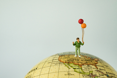 Miniature people figure happy kid  boy holding balloons standing on united states of america map on globe as world climate change or happy United States of american children concept. Stock Photo