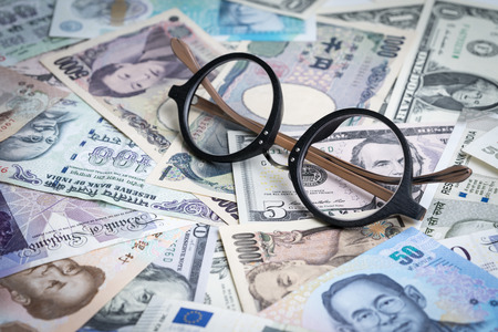 World, global or international financial analysis concept, eyeglasses on pile of major countries banknotes, can be use as forex money exchange trading. Standard-Bild