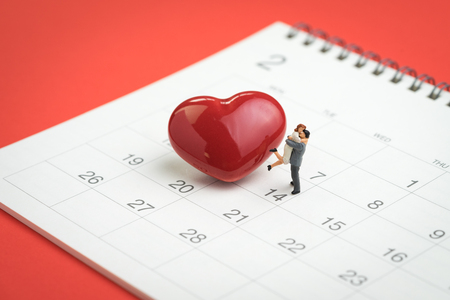 Valentine day concept miniature figures sweet couple standing with shiny red heart shape on 14th February calendar on red background.