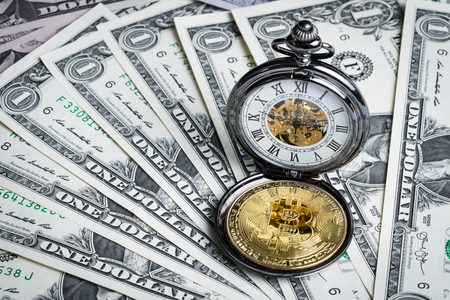 Bitcoin and vintage pocket watch on money dollar banknotes using as time for crypto currency concept, Bitcoin is the main and most famous of digital currency.