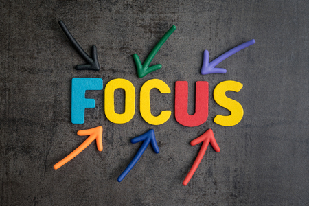 Important of focus in work or life concept, colorful arrows pointing to the word FOCUS at the center on black cement blackboard wall.