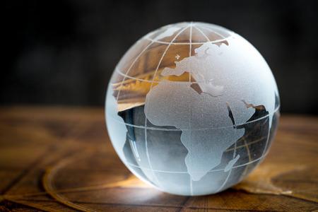 Transparency global, world or international concept with decoration glass globe on vintage book with dark background. Standard-Bild