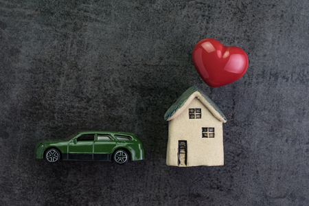 Love house with ceramic miniature house and red heart shape and toy car on dark blackboard in flat lay top view using as Valentines day or romantic living family.