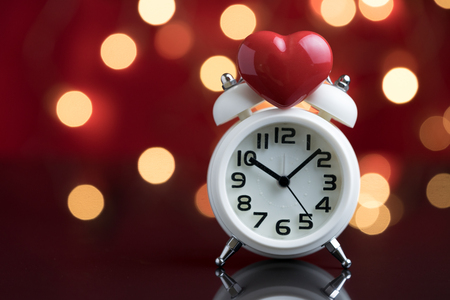 Red heart shape on top of white alarm clock with party decoration light bokeh in the red background using as time for love or wake up after Valentines party.
