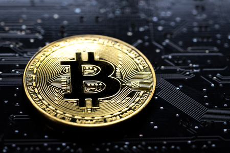 Bitcoin crypto currency digital money concept, shiny golden physical bitcoin coin with B sign on technology and electronics look circuit board in low key black lighting. Standard-Bild