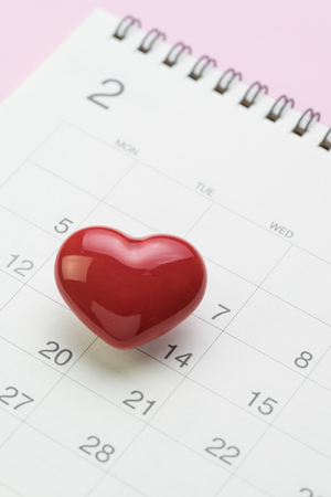Romantic Valentine day card calendar concept, clean white Feb page with cute shiny ceramic red heart shape on 14th February on pink background. Standard-Bild