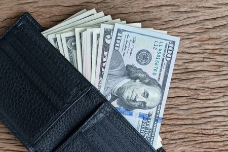 Pay or bonus concept with pile of US dollar banknotes in black leather wallet on wood table.