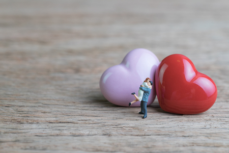 Miniature people sweet couple with red and pink heart shapes on wooden table using as Valentines or wedding card and background with copy space.