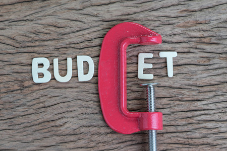 Finance, economy and business squeezing idea, wooden alphabet of the word BUDGET using red clamp as G letter on wooden table, crisis and depression of company money.