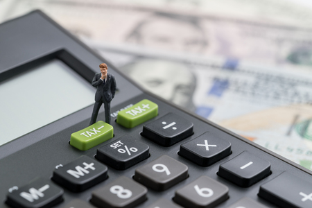 Miniature people business man thinking and standing with TAX minus button on calculator with background of blurred US Dollar banknotes, United States government tax overhaul, cuts or reduce concept. Stock Photo