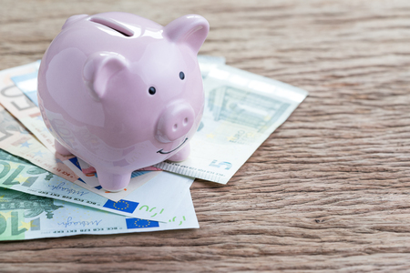 Money savings financial account, Europe economics concept, pink piggy bank on pile of Euro banknotes on wooden table, future growth of compound interest in saving or investing idea. Standard-Bild