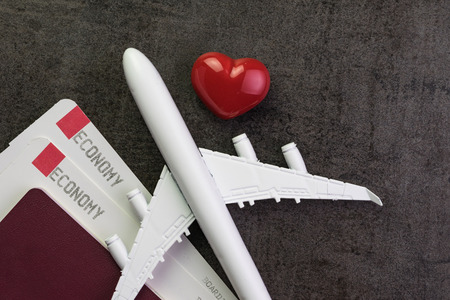 Travel lover, honeymoon trip or valentines gift concept, toy airplane, boarding pass and passport with red and pink heart shape on black texture chalkboard with copy space. Standard-Bild