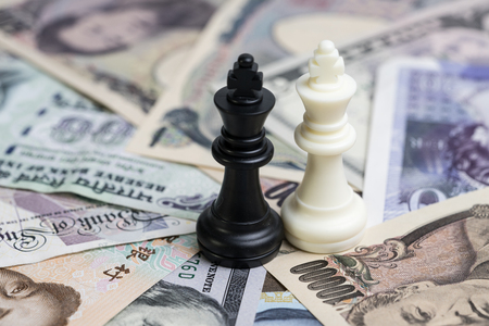 Win-win situation world money finance strategy, white and black winner chess king on international major countries banknotes, US dollar, Japanese yen, Euro, Chinese yuan.