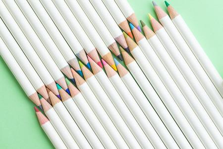Children coloring equipment, pastel pencils color arrange on pale green paper background using as education or art concept.