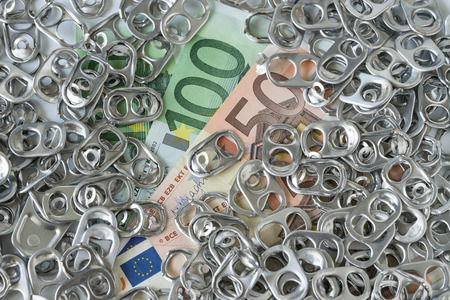 Rich eco junk recycle or green world concept with pile of hoop can opener or pull ring on money Euro banknotes.