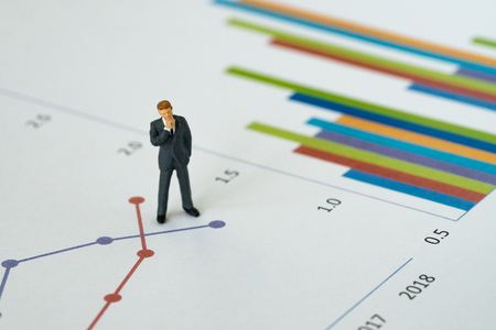 Business yearly performance review concept, miniature people figure businessman standing and thinking on printed analysis chart or graph infographic.