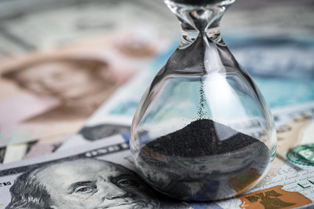 Time counting down for world financial crisis concept, sandglass or hourglass on US dollar money and world international banknotes, can use as long term investment or savings for future.
