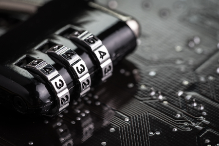 Digital cyber safety or security encryption concept, code numbers on combination pad lock on computer circuit board with solder, technology to encode online information or data protection.