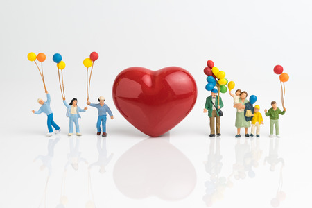 Happy Valentines day card or wallpaper concept, miniature people happy love family holding balloons with red heart shape on white background.