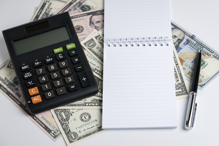 Business accounting or tax calculation concept, white paper notepad and pen, calculator on dollar banknotes money on white table, can be use as revenue, profit and budget.
