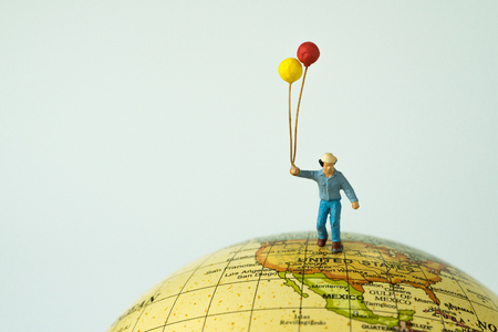 Miniature people figure happy man holding balloons standing on united states of america map on globe as world climate change or happy United States of american citizen concept. Standard-Bild