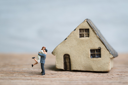 Success marriage love life with miniature lovely couple, happiness husband and wife with house on wood table with copy space.