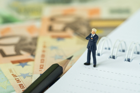 Success financial business leader concept by miniature figure businessman as a proud leader standing  on white paper notepad and pile of Euro banknotes. Standard-Bild