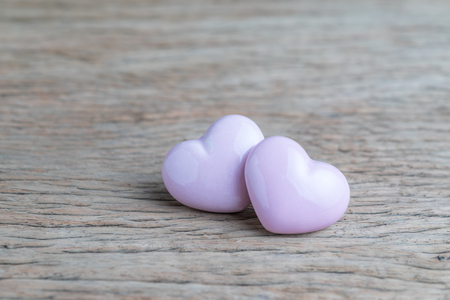 Valentines or wedding background, 2 pink heart shapes on wooden table with copy space, using as love wallpaper, minimal love greeting concept.