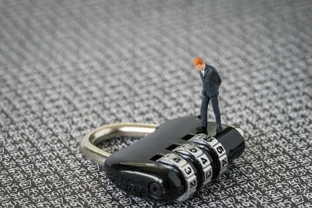 Security impact, safety for business concept, with miniature figure businessman standing and looking at combination lock pad with background of numbers secret code.