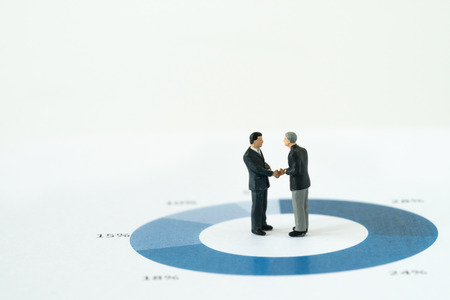 Agreement or deal for business success, miniature executive businessmen handshaking on printed performance pie chart or graph with copy space and seamless white background. Standard-Bild
