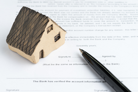 House or real estate buy and sell mortgage concept, miniature house on printed paper document and pen to sign agreement contract, idea of property invest for future high rising price low risk.
